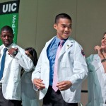 Two men recieve their white coats