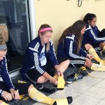 Women's soccer team putting on gold socks