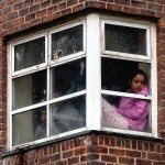 girl sitting in window looking down