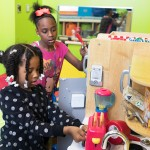 girls playing with a play kitchen