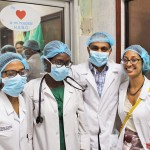 Group of doctors or medical students in lab coats wearing masks and hairnets