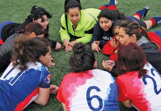 women's rugby team gathered for a meeting on the grass