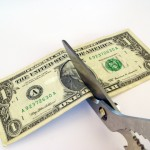 scissors cutting a dollar bill