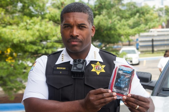 Chief Booker wearing a body cam and holding a pocket pack