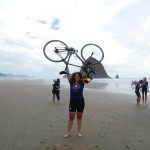 Amanda Koch holding her bike abover her head on a beach