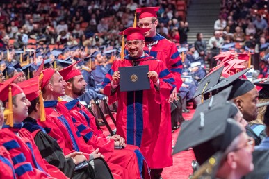Master's student holding his degree