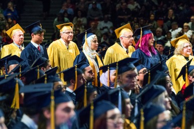 men and women standing in line wearing graduation caps and gowns