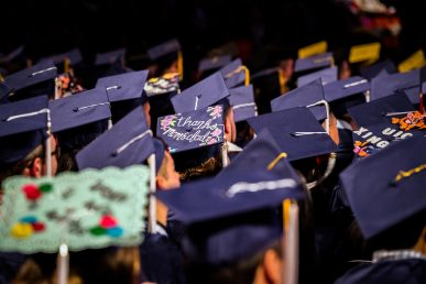 "view of graduates' hats, one reading ""thanks mom and dad"""