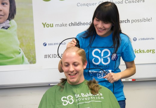 women shaves the head of a man for charity
