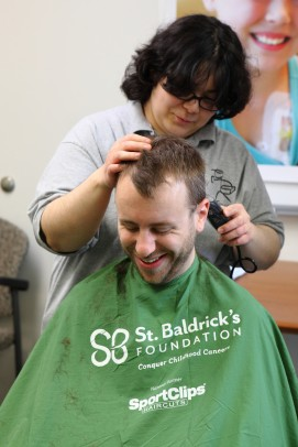 woman shaving the head of a man for St. Baldrick's Foundation