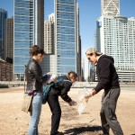 students cleaning up trash on a beach