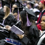 student reading commencement program