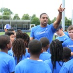 Curtis motioning to stations with group of kids