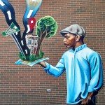 Mural of an African American man holding up a map that has turned 3-dimensional
