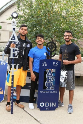 Fraternity members with sign and Greek letters