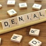"Scrabble tiles spelling out ""denial"""