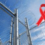 barbed wire fence with a red ribbon representing HIV/AIDS awareness