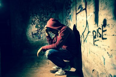 Young person crouched down in a dark corner