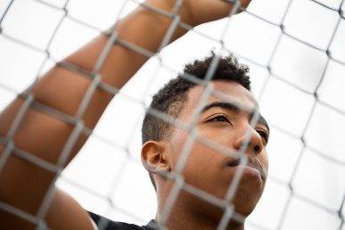 young man seen through a fence