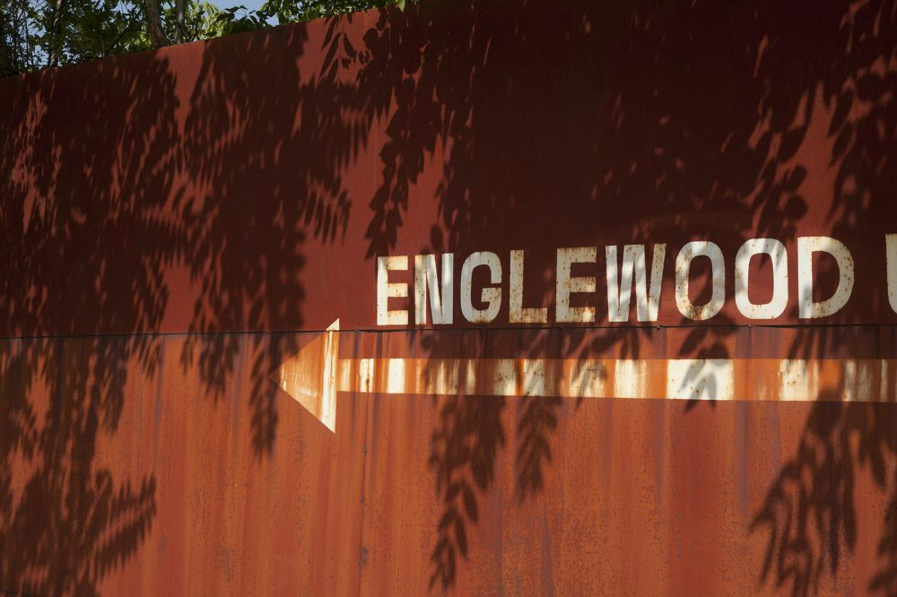 "Fence with ""Englewood"" and an arrow pointing left"
