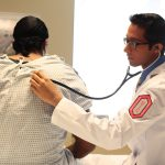 Doctor listening to lung sounds using stethoscope