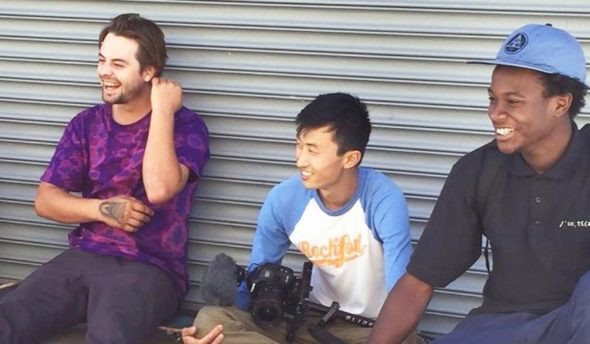 "Bing Liu sitting with actors on the ""Minding the Gap"" set."