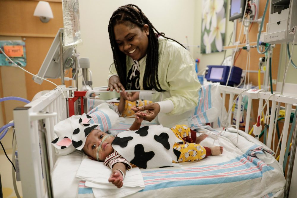 Tiayanna James smiles at her son I'mari in his cow costume during the UI Health pediatrics Halloween party Thursday, October 31, 2019, at University of Illinois Hospital. The NICU dressed all the babies in barnyard themed costumes this year.