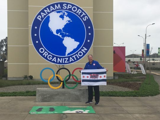 Dr. Mark Hutchinson holding a UIC Flames flag at the 2019 Pan American Games in Lima.