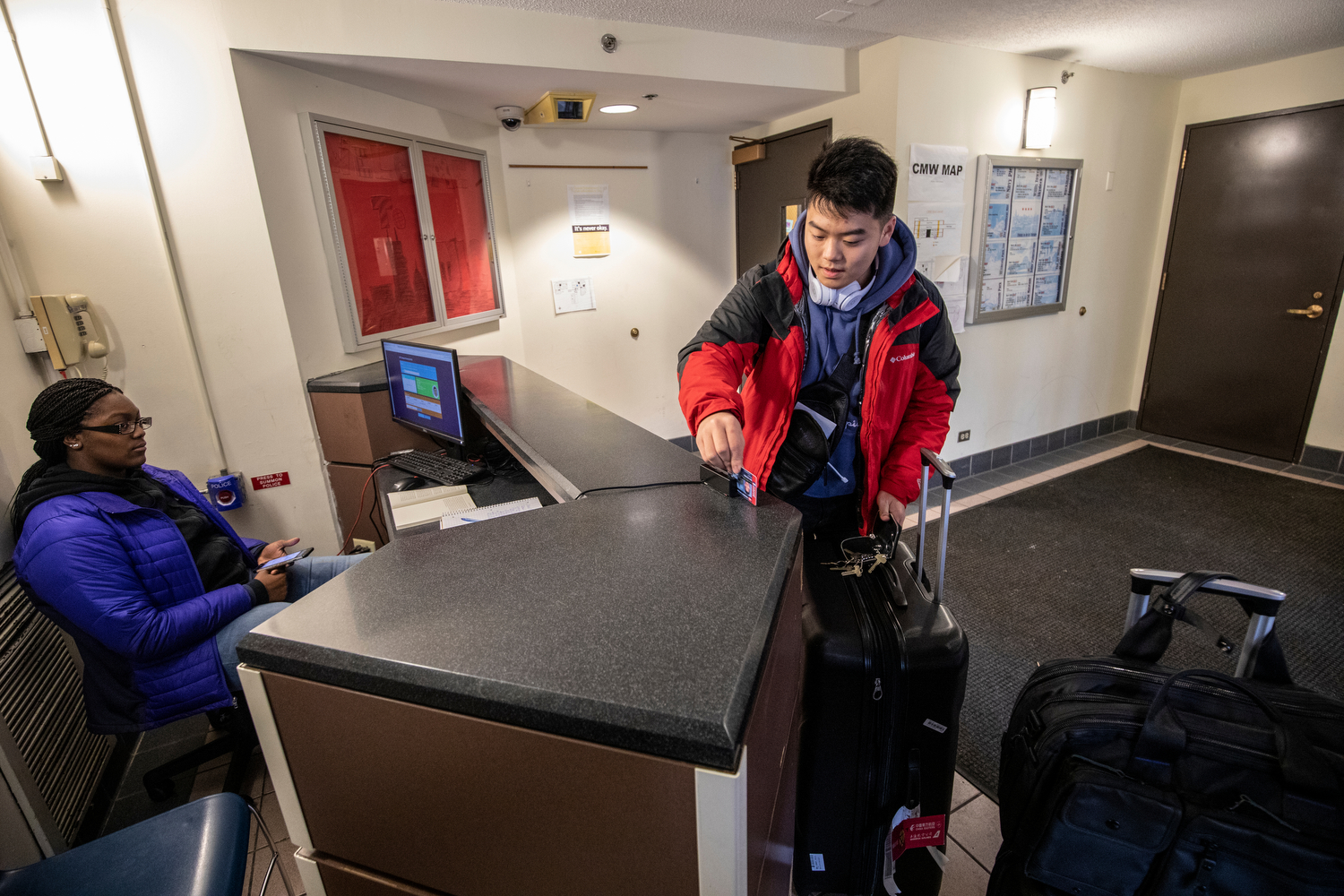 Freshmen Yuchen Shi, right, checks back into the dorms at Student Residence and Commons West on the first day of spring semester after returning from his home in Shanghai, China.