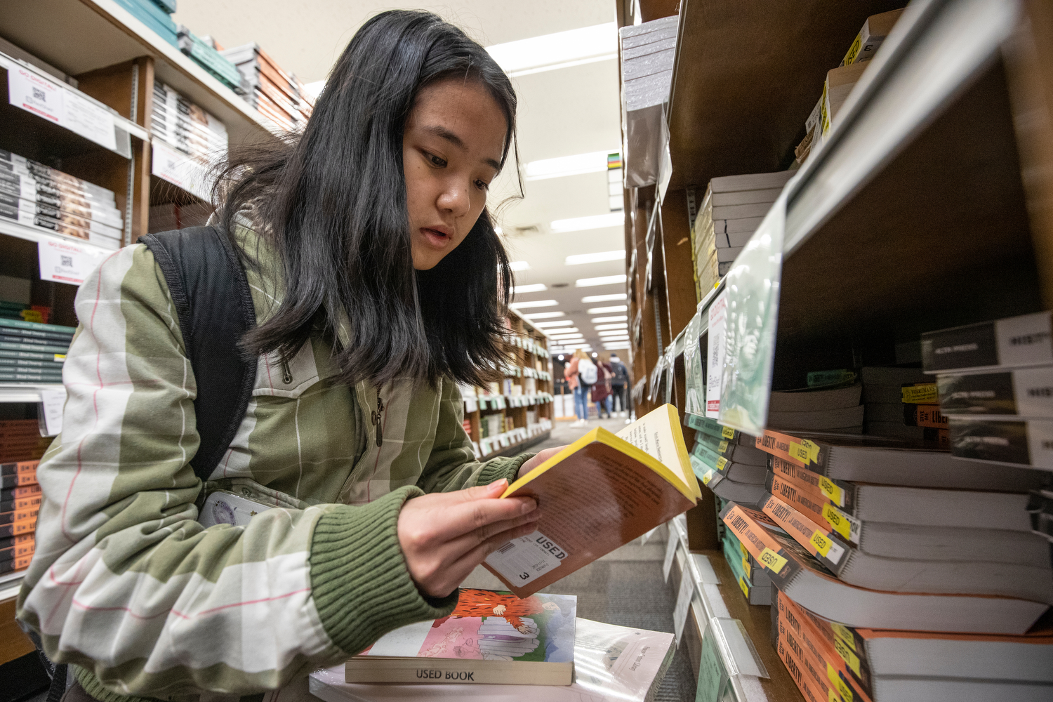 Transfer student Cathy Ouyang (EDU '22) looks at books for her history class at the bookstore in Student Center East during her first day on campus.
