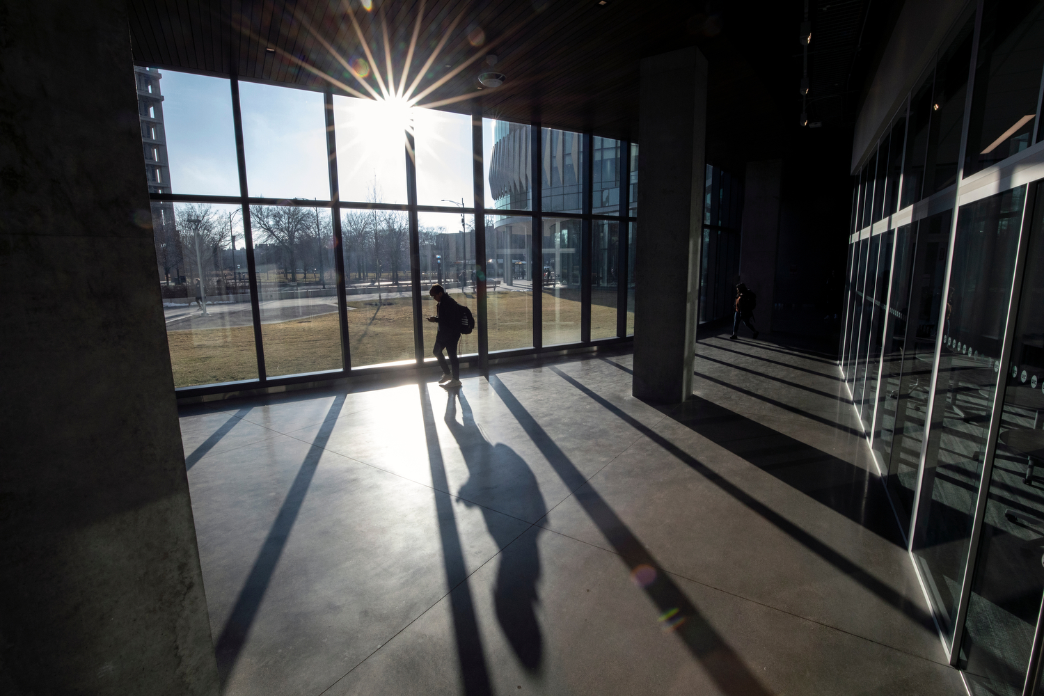 A student walks through the Academic and Residential Complex as the sun peaks through the clouds Tuesday evening.