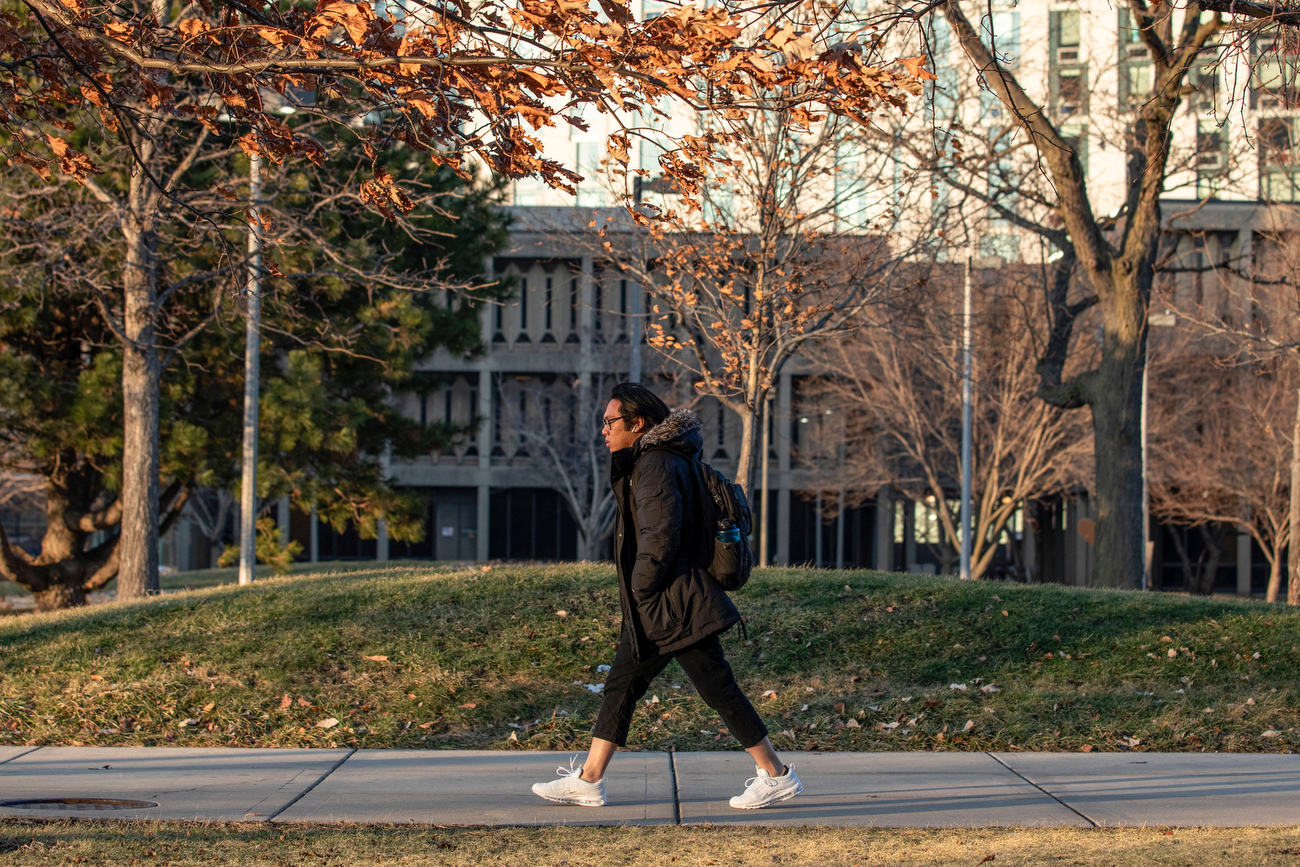 A student walks briskly into the wind outside Stevenson Hall as the sun sets on another day.