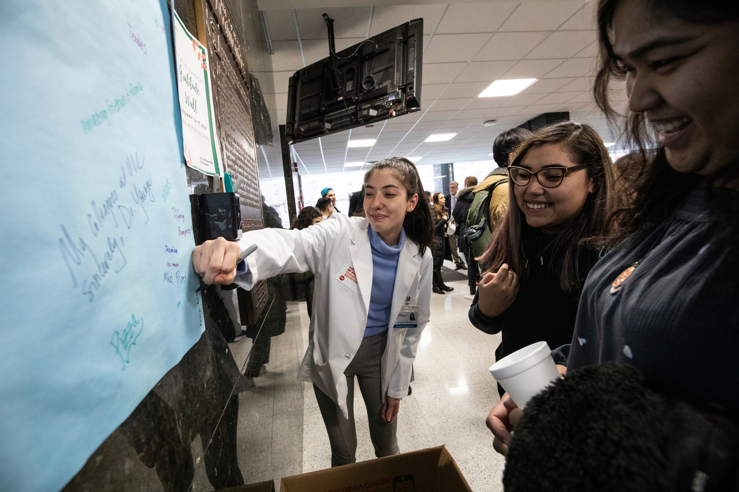 """Amanda McCrone (PHARM '23), center, writes the names of her friends, Yoselin Flores and Anna Lisa Russell, right, on a """"gratitude wall"""" during a welcoming event for pharmacy students at the college."""