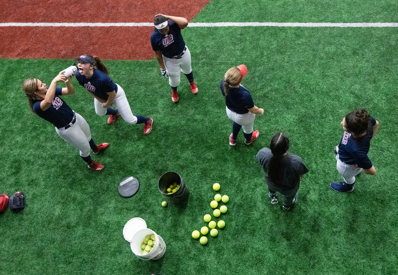 Softball outfielders take a water break during an evening practice on Thursday in the Flames Athletic Center. Spring sport teams started their official practices this week.