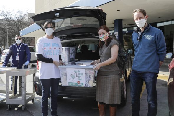 Chicago's First Lady Amy Eshleman, left, helps Rebecca Rugg, dean of the College of Architecture Design and the Arts, and Chris Plevin of the Chicago Shakespeare Theater deliver 5,000 fabric face masks to the University of Illinois Hospital April 3.