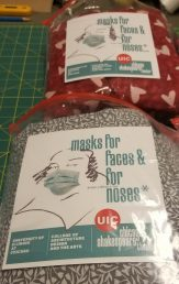 A bag of finished masks displays the UIC and Chicago Shakespeare Theater logos