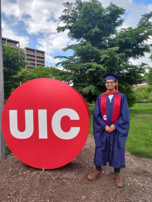 Anoop Nagabhushana, dressed in graduation attire, stands next to the UIC button sculpture in Memorial Grove.
