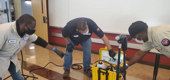 Building Service supervisor Francisco Torres (center) helps building service workers Everett Johnson and Clarence Williams prepare to sanitize a lecture hall using a new electrostatic decontamination unit.