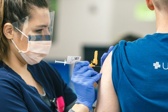 A woman wearing a face mask and a face shield puts a vaccine needle into a man's arm.