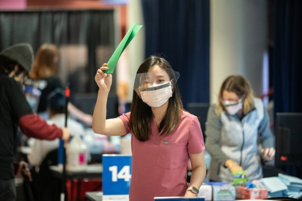 Dentistry student Ellie Park signals she's available to administer another vaccine on Monday, Feb. 1, 2021, at the University of Illinois Chicago Credit Union 1 Arena. (Joshua Clark/University of Illinois Chicago)