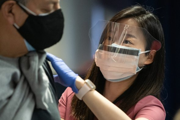 Dentistry student Ellie Park administers COVID-19 vaccinations at the Credit Union 1 Arena on Monday, Feb. 1, 2021, at the University of Illinois Chicago. (Joshua Clark/University of Illinois Chicago)