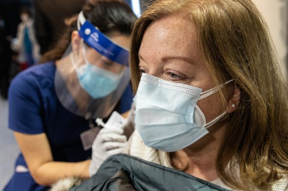 Donna Buchanan receives the COVID-19 vaccine in the Credit Union 1 Arena on Monday, Feb. 1, 2021, at the University of Illinois Chicago. Nursing student Maria Escamilla administers the shot. (Joshua Clark/University of Illinois Chicago)