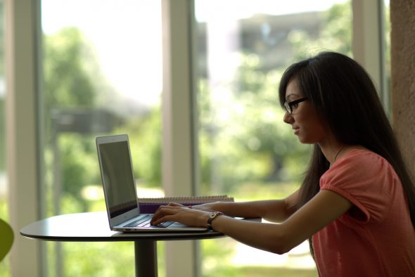 Female with long dark hair sits at a small table using her laptop