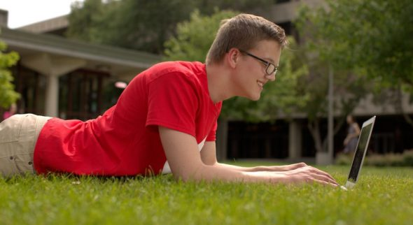 Male student laying in the grass using a laptop