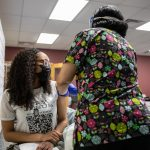 Sania White gets her first shot of the Moderna COVID-19 vaccine at the Mile Square Health Center in Englewood.