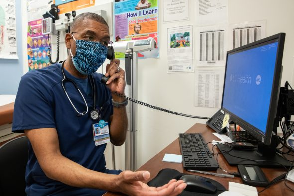 Dale Benton, certified nurse practitioner and site medical director, makes a call between seeing patients and encouraging people to get vaccinated at UI Health Mile Square Health Center in Englewood.