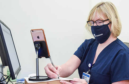 A female nurse wearing a UIC Nursing face mask and navy scrubs writes with a pen and paper and has an iPhone on a holder in front of her.