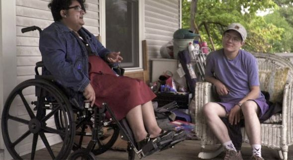 "Marrok Sedgwick, right, in a still from his film ""People Like Me."" Image shows two people, one sitting in a wicker chair and one in a wheelchair, having a conversation."