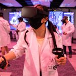 """Actor Stephanie Shum who plays Aya in """"Hummingbird"""" navigates the virtual reality stage wearing a VR headset."""