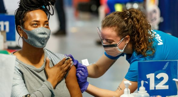 A woman receives her COVID-19 vaccine from a nurse.
